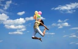 Vôo da mulher nova com balões coloridos Imagem de Stock