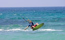Vôo de Kitesurfer através do ar em uma praia ensolarada Imagem de Stock