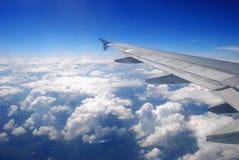 Vôo plano da asa acima das nuvens imagens de stock