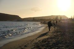 Völker, die in den Strand bei Sonnenuntergang gehen stockbild