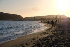 Völker, die in den Strand bei Sonnenuntergang gehen lizenzfreie stockbilder