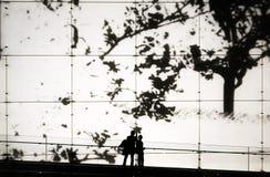 Völker silhouettieren auf Schirmwandhintergrund stockfotografie