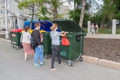 Völker werfen Abfall im neuen Plastikmüllcontainer Stockfotografie