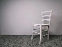 Völlig grauer Raum mit leerem Stuhl- und Kopienraum stockfoto