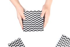 拿着黑白V形臂章礼物盒的手 库存图片