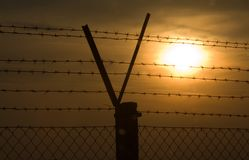 V. Sunset at a security fence Stock Photography