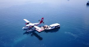 V06387 Aerial flying drone view of Maldives white sandy beach airplane seaplane sunny tropical paradise island with aqua Stock Photos