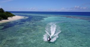 V06200 Aerial flying drone view of Maldives white sandy beach jetski riding sunny tropical paradise island with aqua stock video footage
