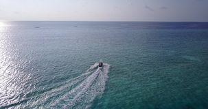 V06164 Aerial flying drone view of Maldives white sandy beach jetski riding sunny tropical paradise island with aqua. Aerial flying drone view of Maldives white Stock Images