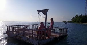 V03828 Aerial flying drone view of Maldives white sandy beach 2 people young couple man woman relaxing on sunny tropical Stock Photo