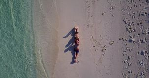 V04010 Aerial flying drone view of Maldives white sandy beach 2 people young couple man woman romantic love on sunny. Aerial flying drone view of Maldives white Stock Photo