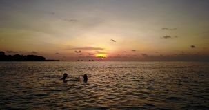 V04135 Aerial flying drone view of Maldives white sandy beach 2 people young couple man woman romantic love sunset Stock Photos