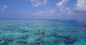 V04066 Aerial flying drone view of Maldives white sandy beach 2 people young couple man woman snorkeling swimming diving Royalty Free Stock Images