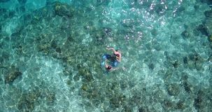 V04073 Aerial flying drone view of Maldives white sandy beach 2 people young couple man woman snorkeling swimming diving Royalty Free Stock Image