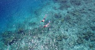 V04051 Aerial flying drone view of Maldives white sandy beach 2 people young couple man woman snorkeling swimming diving Stock Photos