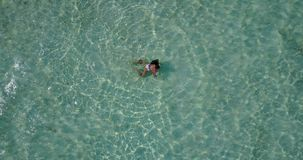 V06313 Aerial flying drone view of Maldives white sandy beach 1 person young beautiful lady swimming splashing on sunny Royalty Free Stock Photo