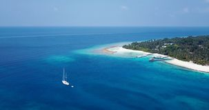 V03007 Aerial flying drone view of Maldives white sandy beach on sunny tropical paradise island with aqua blue sky sea stock video