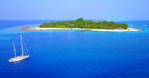 V03422 Aerial flying drone view of Maldives white sandy beach on sunny tropical paradise island with aqua blue sky sea stock video
