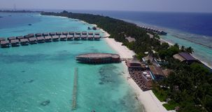 V03670 Aerial flying drone view of Maldives white sandy beach on sunny tropical paradise island with aqua blue sky sea stock footage