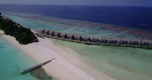 V03555 Aerial flying drone view of Maldives white sandy beach on sunny tropical paradise island with aqua blue sky sea stock video footage