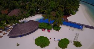 V06695 Aerial flying drone view of Maldives white sandy beach swimming pool in luxury 5 star resort hotel relaxing. Aerial flying drone view of Maldives white stock video footage
