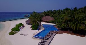 V06707 Aerial flying drone view of Maldives white sandy beach swimming pool in luxury 5 star resort hotel relaxing. Aerial flying drone view of Maldives white stock footage