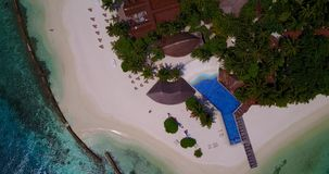 V06741 Aerial flying drone view of Maldives white sandy beach swimming pool in luxury 5 star resort hotel relaxing stock video footage