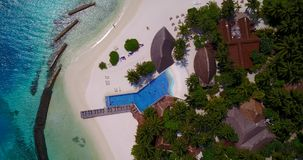 V06687 Aerial flying drone view of Maldives white sandy beach swimming pool in luxury 5 star resort hotel relaxing stock footage