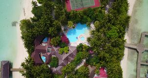 V06735 Aerial flying drone view of Maldives white sandy beach swimming pool in luxury 5 star resort hotel relaxing. Aerial flying drone view of Maldives white stock video