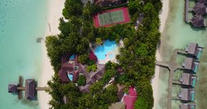 V06736 Aerial flying drone view of Maldives white sandy beach swimming pool in luxury 5 star resort hotel relaxing. Aerial flying drone view of Maldives white stock video