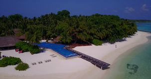 V06677 Aerial flying drone view of Maldives white sandy beach swimming pool in luxury 5 star resort hotel relaxing. Aerial flying drone view of Maldives white stock video