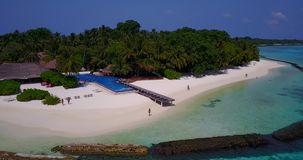 V06714 Aerial flying drone view of Maldives white sandy beach swimming pool in luxury 5 star resort hotel relaxing. Aerial flying drone view of Maldives white stock footage
