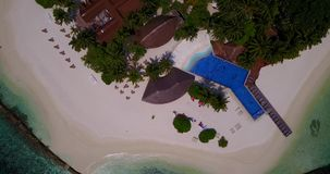 V06692 Aerial flying drone view of Maldives white sandy beach swimming pool in luxury 5 star resort hotel relaxing. Aerial flying drone view of Maldives white stock video