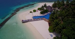 V06745 Aerial flying drone view of Maldives white sandy beach swimming pool in luxury 5 star resort hotel relaxing. Aerial flying drone view of Maldives white stock video footage