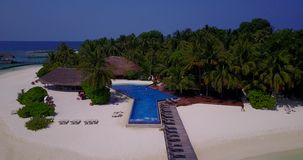 V06682 Aerial flying drone view of Maldives white sandy beach swimming pool in luxury 5 star resort hotel relaxing. Aerial flying drone view of Maldives white stock video