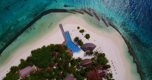 V06694 Aerial flying drone view of Maldives white sandy beach swimming pool in luxury 5 star resort hotel relaxing. Aerial flying drone view of Maldives white stock video