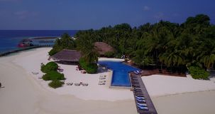 V06738 Aerial flying drone view of Maldives white sandy beach swimming pool in luxury 5 star resort hotel relaxing. Aerial flying drone view of Maldives white stock video footage