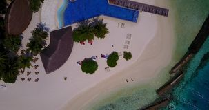 V06675 Aerial flying drone view of Maldives white sandy beach swimming pool in luxury 5 star resort hotel relaxing. Aerial flying drone view of Maldives white stock footage