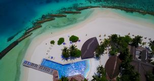 V06733 Aerial flying drone view of Maldives white sandy beach swimming pool in luxury 5 star resort hotel relaxing. Aerial flying drone view of Maldives white stock video
