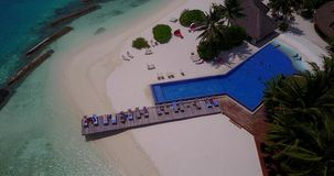 V06748 Aerial flying drone view of Maldives white sandy beach swimming pool in luxury 5 star resort hotel relaxing. Aerial flying drone view of Maldives white stock footage