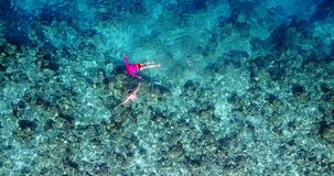V06435 Aerial flying drone view of Maldives white sandy beach young people snorkeling swimming underwater on sunny Stock Photos