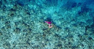V06436 Aerial flying drone view of Maldives white sandy beach young people snorkeling swimming underwater on sunny Stock Photography