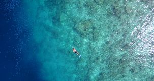V06463 Aerial flying drone view of Maldives white sandy beach young people snorkeling swimming underwater on sunny Stock Photos
