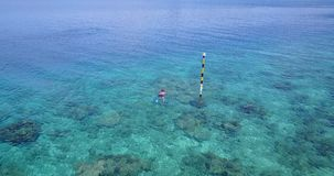 V06439 Aerial flying drone view of Maldives white sandy beach young people snorkeling swimming underwater on sunny Stock Photos