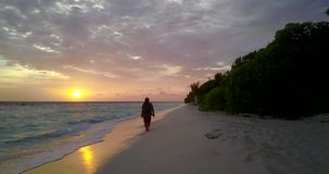 V10713 backpacker traveler girl at sunset sunrise shot in evening in the dark walking and exploring the beach by the sea. Backpacker traveler girl at sunset stock video footage