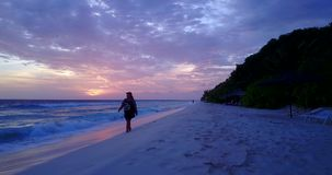 V10730 backpacker traveler girl at sunset sunrise shot in evening in the dark walking and exploring the beach by the sea. Backpacker traveler girl at sunset stock video footage