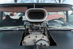 V8 Carburetor. Carburetor on a black V8 car with the hood been cut out for it Royalty Free Stock Photo