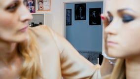 V?deo de la c?mara lenta del primer del artista de maquillaje profesional que trabaja en estudio Visagiste que aplica maquillaje  almacen de metraje de vídeo