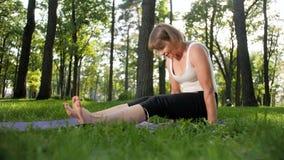 v?deo de la c?mara lenta 4k de la yoga practicante sonriente envejecida centro y de meditar de la mujer en parque en el d?a de ve almacen de metraje de vídeo