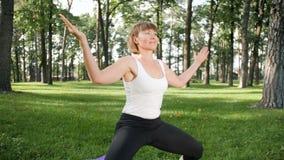 v?deo de la c?mara lenta 4k de la yoga practicante sonriente envejecida centro y de meditar de la mujer en parque en el d?a de ve metrajes